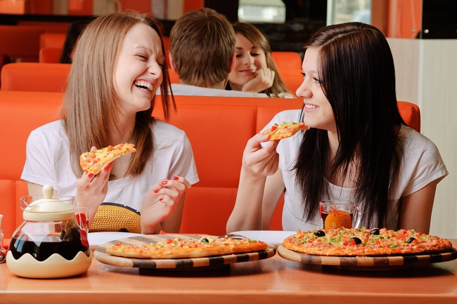 Beautiful young women eating pizza and having fun